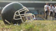 Helmet lying on football pitch, team training at gridiron sports school, hobby Arkistovideo