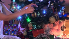A woman decorates a beautiful christmas tree in a house. New Year 2017 Stock Footage