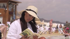 Sexy girl reading a book on the beach. Stock Footage