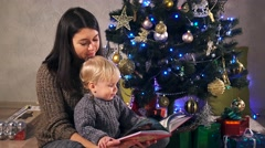 Young mother and her little baby boy son in warm sweaters reading a book Stock Footage