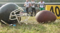 Football helmet and ball lying on pitch, players on a break, professional sports HD Footage