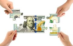 Hands and money puzzle Stock Photos
