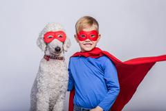 Handsome little superman with dog. Superhero. Halloween Kuvituskuvat