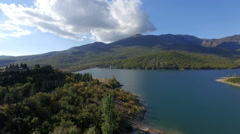 Aerial drone footage of lake and mountains against sky. 4K video Arkistovideo