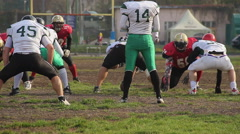 American football players attacking and tackling opponents, scrimmage on pitch Stock Footage