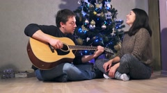 Young happy couple celebrating Christmas. Guy playing guitar, girl listen Stock Footage