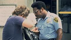 New York 1977: policeman checking inside a man's bag Stock Footage