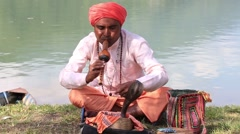 Portrait of snake charmer adult man in turban and cobra sitting near lake, Nepal Stock Footage