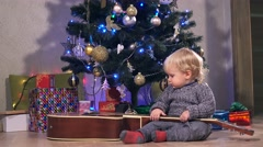 Happy baby boy celebrating Christmas. Little child playing guitar and laugh Stock Footage