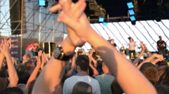 People clap and wave their hands at a rock concert Stock Footage