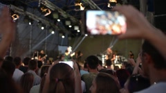 Hands Hold Mobile Camera With Digital Display Among People During Rock Concert Stock Footage