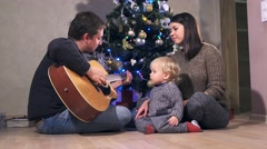 Young happy family celebrating Christmas. Father playing guitar Stock Footage