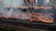 Picnic Roasting sausages on the grill for a big company Stock Footage