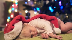 Baby boy in red Santa hat sleeps on couch near Christmas eve. Little Baby sleep Stock Footage