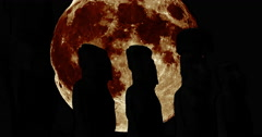 Silhouettes of the Moai with giant moon Stock Footage