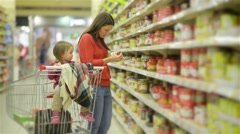 Young Mother and child walks along wholesale shelves and taking goods in shop Stock Footage