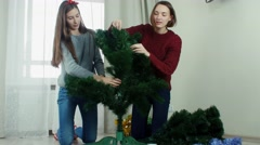 Two young girl preparing Christmas tree for decorations and having fun New year Stock Footage