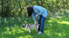 Young woman caresses her dog bulldog in nature Stock Footage