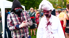 Bloody young man drinking blood - Crowd of zombies preparing for a zombie walk Stock Footage