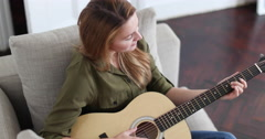 Young adult female playing acoustic guitar Stock Footage