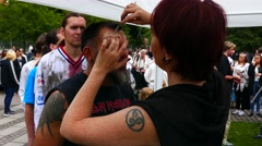 People queuing for make up artist to make wounds on their face for zombie walk Stock Footage