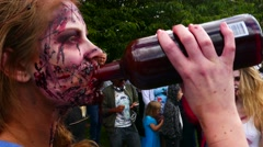 Pan from zombie man to a zombie girl drinking blood, preparation for zombie walk Stock Footage