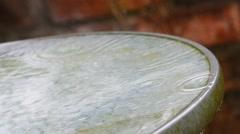 Heavy rain falling on glass garden table uk Stock Footage