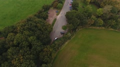 Tilting aerial view following a car through the countryside. Stock Footage