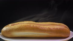 Steaming freshly made hot dog against black background. Worldwide popular fast Stock Footage