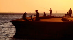 Fishers and cyclists in sunset Stock Footage