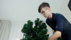 Young man preparing Christmas tree for decorations and having fun New year Stock Footage