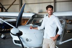 Attractive young man standing near small aircraft Stock Photos
