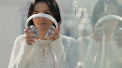Woman in white earphones enjoying to listen music at glassy building Stock Footage
