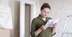 Young adult female choosing colour to paint wall Stock Footage