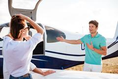 Pilot inviting passengers on board of private airplane Stock Photos