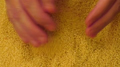 Female hands holding a pot with raw millet Stock Footage