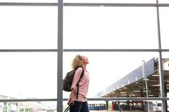 Happy young traveler walking in station laughing Stock Photos