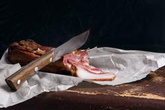 Close up view slices of smoked bacon and knife on the white packaging paper. Stock Photos