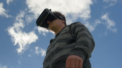 Fluffy clouds pass behind man wearing Virtual Reality headset Stock Footage