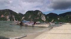 Motor thai long tail wooden boat anchored at sea coast Stock Footage