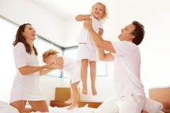 Happy young family playing in the bedroom Stock Photos