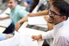 Happy student with exam test or handout at lecture Stock Photos