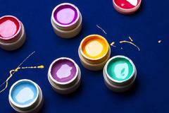 Cans of paint for creativity on a blue velvet table. Yellow paint spilled on  Stock Photos