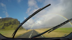 Iceland brilliant double rainbow over road green mountains driving POV 4k Stock Footage