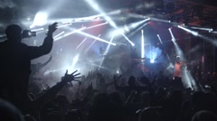 Festival crowd dancing jumping up for music drop lasers slow motion Stock Footage