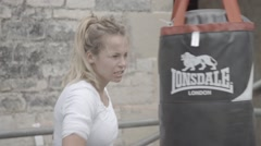 Pretty girl boxing punch bag exterior Stock Footage