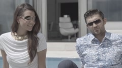 Pretty girl man model posing to camera both sunglasses sat down Stock Footage