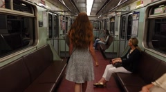 Young woman go in almost empty subway car, POV camera follow behind Stock Footage