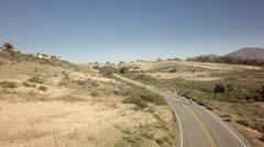 Drone view of bike race on open road with mountains in background 4 Stock Footage