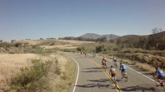 Drone view of bike race on open road with mountains in background 10 Stock Footage